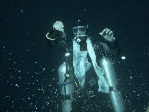 Sidemount diver doing a poja underwater to the sea gods